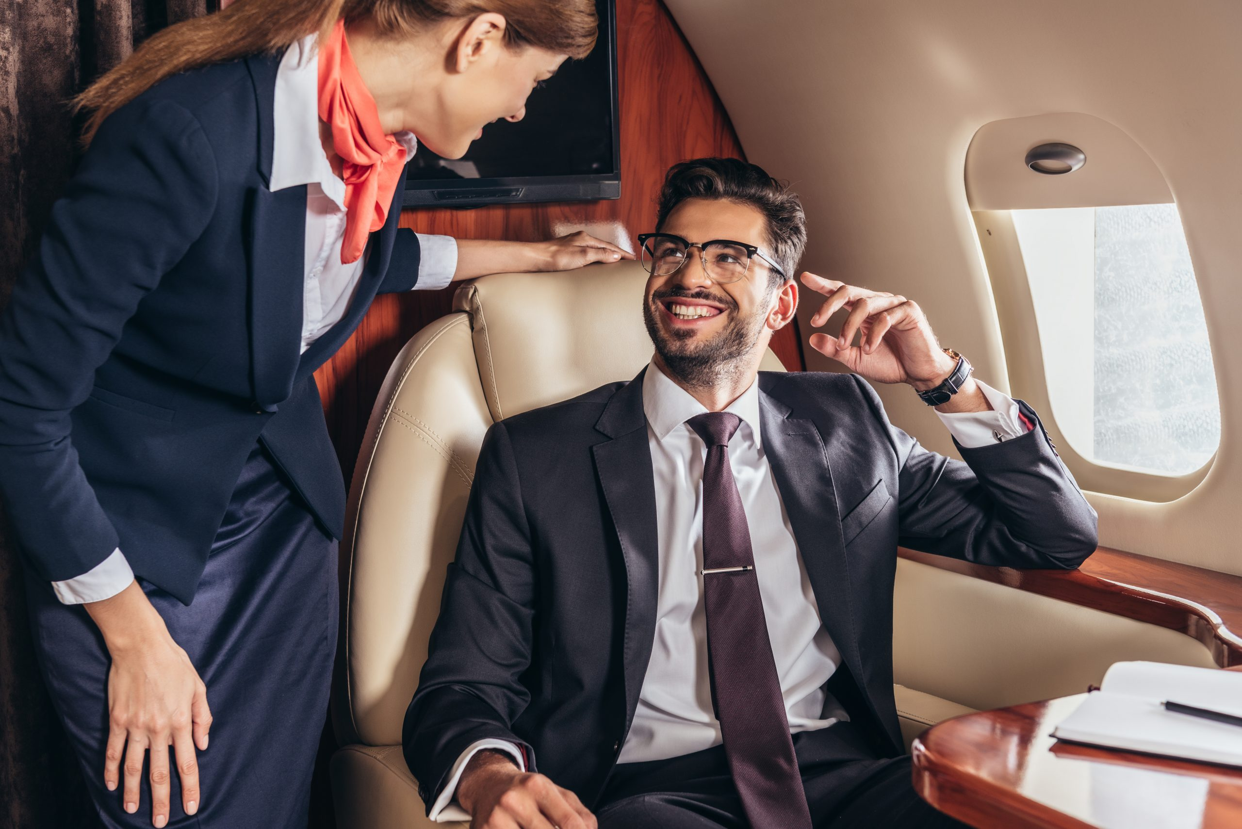 smiling businessman in suit looking at flight attendant in private plane